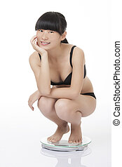 Beautiful woman weighing herself isolated on white -...