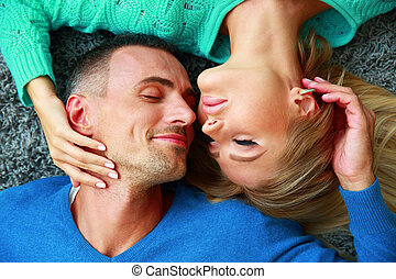 Happy young couple lying on the carpet