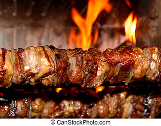 spit roast with meat cooked on a spit in the fireplace 1 -...