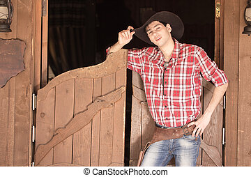 Cowboy in hat standing near saloon entrance, outdoors