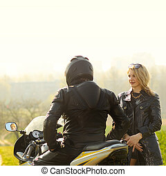 Beautiful blonde with a biker posing near a sports bike. Beautiful couple with a motorcycle at sunset