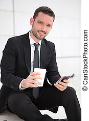 Portrait of an attractive businessman sending texts - View...
