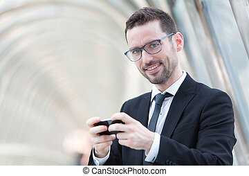 Attractive Businessman sending a text during a break - View...