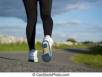 Low angle close up female walking on road with sneakers
