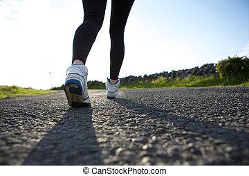 Woman walking in sneakers on street