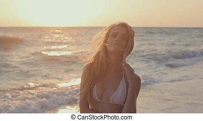 Young girl walking near the sea shore on sunset and smile -...
