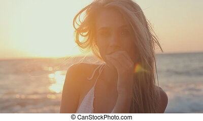 Gorgeous young girl with a beautiful figure in  swimsuit near the sea at sunset