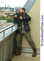 Armed man with weapon aiming from abandoned building