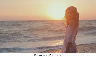 Seductive girl withe long hair posing at sunset on the beach...