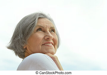 Senior woman on the background of sky - Portrait of a...