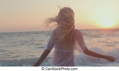 Young seductive girl with long hair in a white tunic stands at sunset near the sea