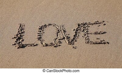 "Word ""Love"" drawn in the sand - Word ""Love"" deleting ocean..."