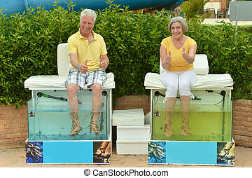 Senior couple on procedure for foot care in a special small...