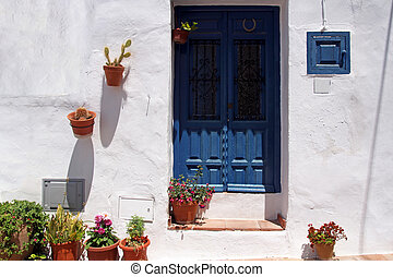 front side of typical spanish house with blue wooden door...