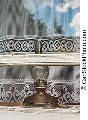 old kerosene lamp in the window of the house