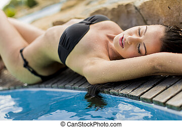Young woman laying by the pool