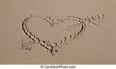 Love sign heart with an arrow written on sand with ocean...