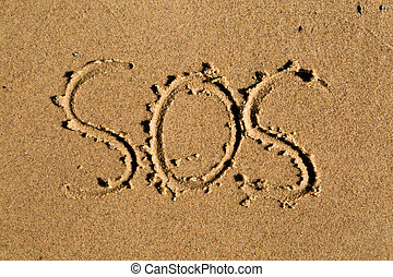SOS - Casual writing in the wet sand on a sunny day.