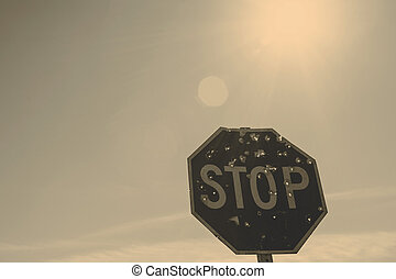 Stop sign with holes from bullets