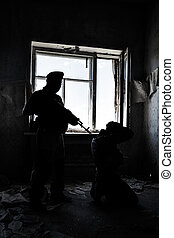 hostage taking - Backlit image of soldier guarding a hostage