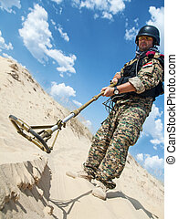 soldier with metal detector - iraqi soldier in the desert...