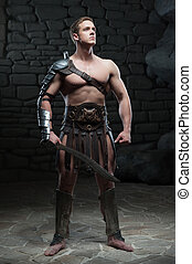 Gladiator with sword posing - Full length portrait of young...