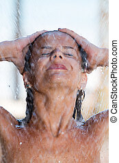 woman in tropical shower in the summertime focused on the...