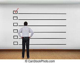 checklist - businessman in office looking at wall with...