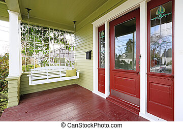 Entrance porch in red and green color with hanging swing -...