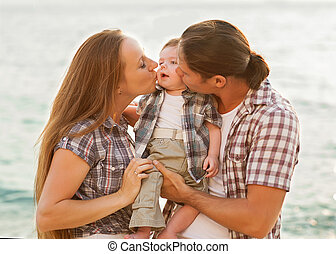 Happy mother, father and daughter in sunset
