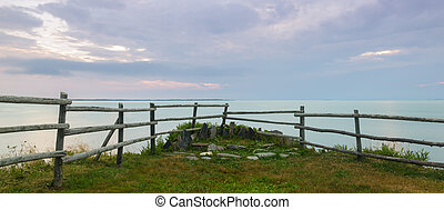 Panorama of a wooden fence on ocean shore in the morning...