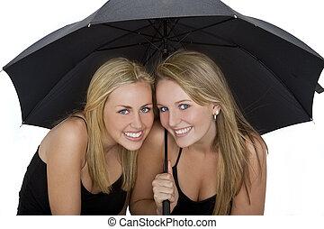Two Beautiful Young Women Under An Umbrella - Studio shot of...