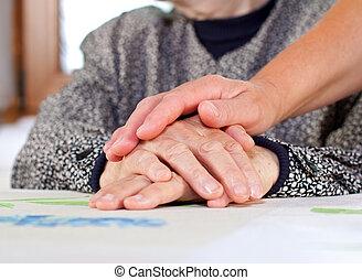 Wrinkled hands - Doctors hand holding a wrinkled elderly...
