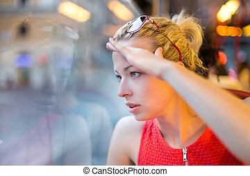 Woman looking out tram's window. - Thoughtful lady riding on...