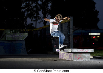 Inline Skater doing a grind on bench at night