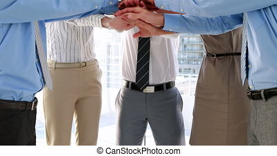 Team putting their hands together - Business team putting...