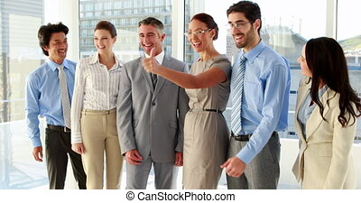Team showing thumbs up to camera - Business team showing...