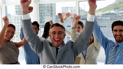 Business team cheering at camera - Excited business team...