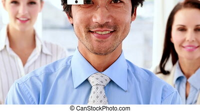 Businessman smiling at camera wearing smart glasses in the...