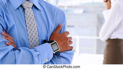 Businessman smiling at camera wearing a smart watch in the...