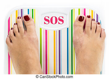 """Feet on bathroom scale with word """"SOS"""" on dial"""