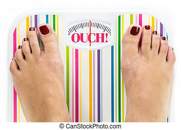 Feet on bathroom scale with word quot;Ouchquot; on dial -...