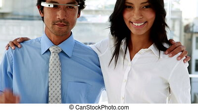 Business partners smiling at camera together with smart...