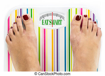 Feet on bathroom scale with words quot;Eat smartquot; on...