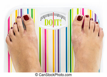 Feet on bathroom scale with words quot;Do itquot; on dial -...