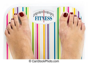 Feet on bathroom scale with word quot;Fitnessquot; on dial -...