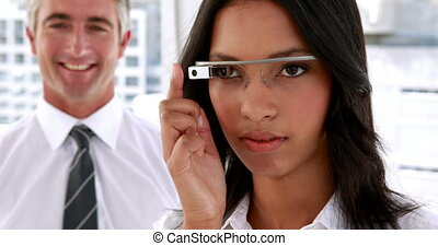 Businesswoman smiling at camera using smart glasses in the...