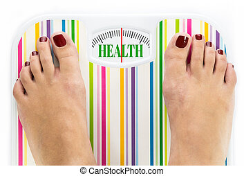 Feet on bathroom scale with word quot;Healthquot; on dial -...