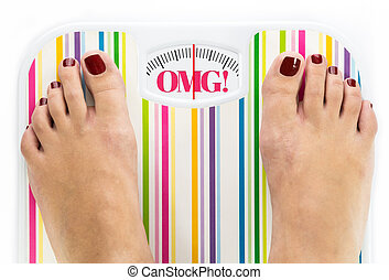 Feet on bathroom scale with word quot;OMGquot; on dial -...