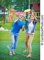Throwing disc - Young couple playing with flying disc in the...